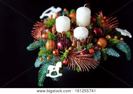 Winter table centerpiece wreath with candles newyear toys spice and fir branches