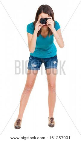 young woman in shorts photographed something compact camera. Isolated over white background.