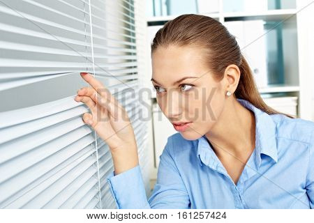 Young businesswoman peeping through jalousie in office