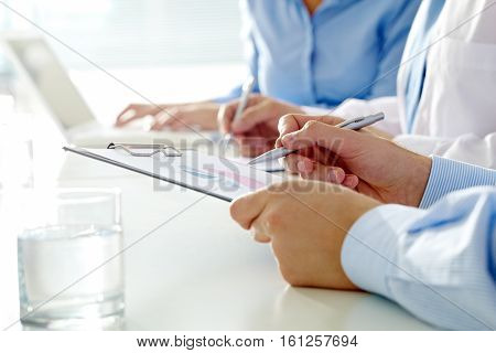 Male hands making notes on spreadsheet in office