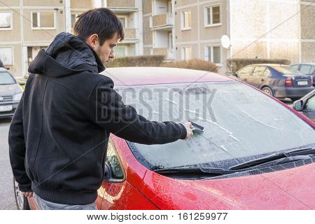 Man Is Scraping Ice From Frozen Windshield Window Of Car In Wint