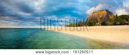 White sandy beach and Le Morne Brabant at sunset. Mauritius. Panorama