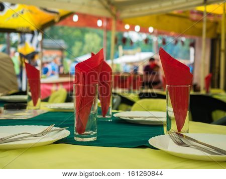 Picture of the dining-table served with red napkin. White plates with flatware and red napkin against the blurred background of the guests of a restaurant. Plates, flatware, glass and red napkin.