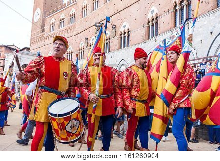 SIENA ITALY - JUNE 29 2016: Men in historical colorful costumes ready to celebrate and parade at traditional Palio horse race in Siena Italy