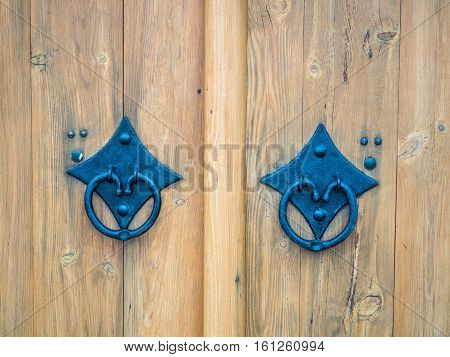 Picture of the double door with blue door handle close up. Background of the bright coloured wooden gate with blue door handle. Texture of a wooden gate close up.