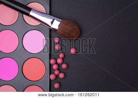 Blushes palette blusher balls and brush for makeup on black slate background