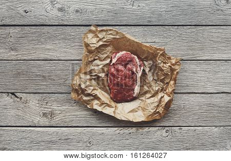 Raw beef steak in craft paper on dark wooden table background, top view. Fresh juicy meat food. Cooking ingredients, butcher's and grocery concept, filtered image