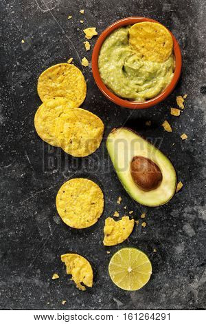 Mexican nachos chips with homemade fresh guacomole sauce over old  background. Top view. With space for text