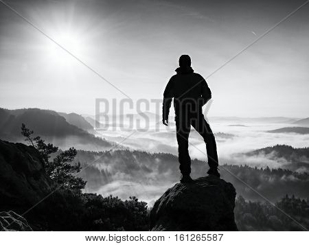 Hiker Climbed On Peak Of Rock Above Valley. Man Watch Over Misty And Foggy Morning Valley