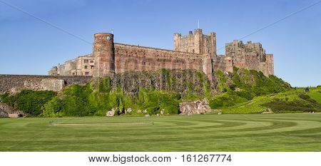 Bamburgh Castle, on the coast at Bamburgh, Northumberland, England, is a Grade I listed building. This is a view from the land side.