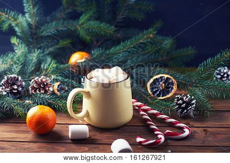 mug with hot chocolate, christmas tree, tangerines, peppermint stick and marshmallow on a wooden background. Dark photo. Empty space for text. Toned for art effect
