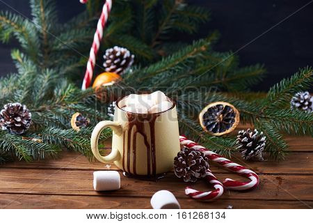 mug with hot chocolate with dripping chocolate, christmas tree, tangerines, peppermint stick and marshmallow on a wooden background. Dark photo. Empty space for text. Toned for art effect
