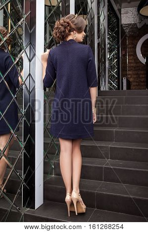 Beautiful Young Girl Model Costs Back In Dark Blue Dress On A Background Of A Wall Mirror, Makeup