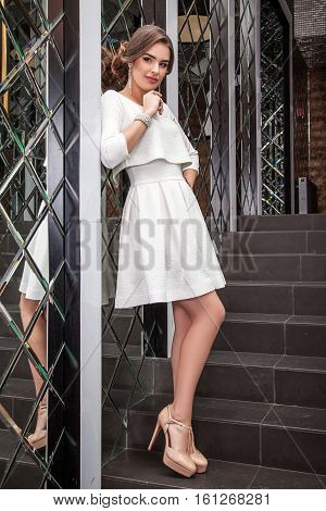 Beautiful Young Woman Model Standing In A White Dress On A Background Of A Wall Mirror, Makeup