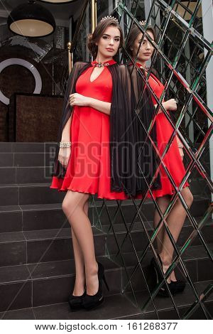 Beautiful Young Girl Is A Model In A Red Dress On A Background Of A Wall Mirror, Makeup