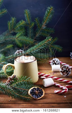 Close view at mug with hot chocolate, christmas tree, tangerines, peppermint stick and marshmallow on a wooden background. Dark photo. Vertical shot