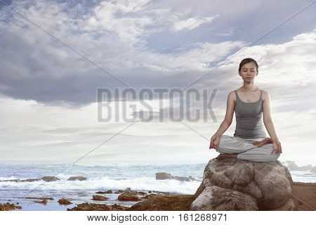 Portrait Of Asian Woman Sitting Over The Rock Doing Yoga