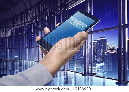 Business Hand Holding A Smartphone With Number 2017 On The Search Bar