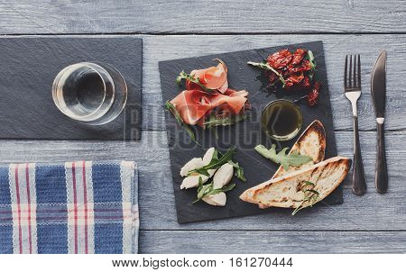 Catering platter antipasto with ham prosciutto, bruschetta bread toasts and mozzarella cheese on stone desk on blue wood served table top view with copy space. Served starter meals, restaurant food