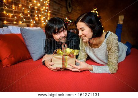 The young couple exchanges gifts. The beautiful man and the woman lie on a bed. Before them a box with a gift in beautiful packing. Young people look with love and tenderness at each other.
