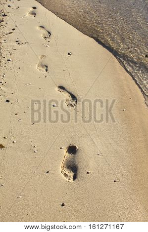 Nature background with transparent sea water and footprints in the sand at the beach