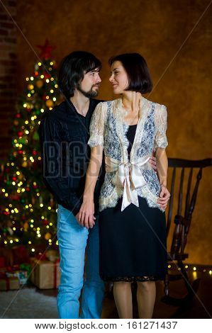Beautiful young couple stands near the Christmas tree. Young people with love and tenderness look at each other. Under the Christmas tree there are a lot of gifts in beautiful boxes.