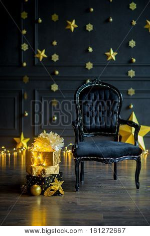 Waiting for a holiday. The beautiful velvet armchair is in festively decorated room. On a dark wall the gold shining garlands. Gifts in elegant boxes festive accessories lie on a floor.