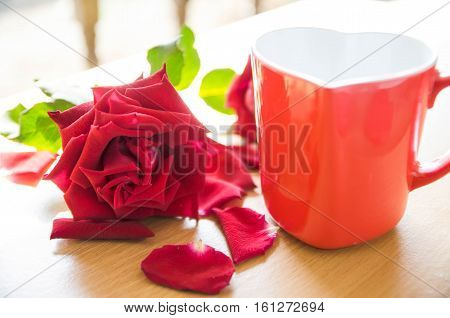 Cup of coffee with red heart-shaped rose petals.