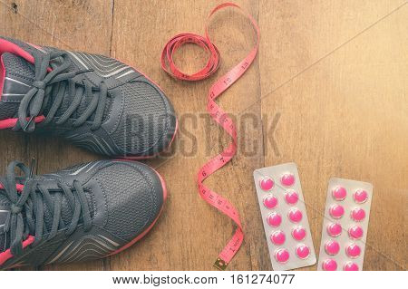 Sports sneaker shoe with measuring tape and blisters of medical pills on wood background. Fitness healthy and active lifestyles Concept