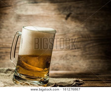 Foamy beer poured into mug standing on wooden table