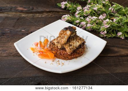 Fish coated in crumbs on vegetable cushion with squash, tomatoes, carrots and onions