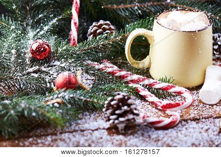 mug with hot chocolate, christmas tree, tangerines, peppermint stick and marshmallow on a snow wooden background with falling snow. Dark photo. Empty space for text. Selective focus
