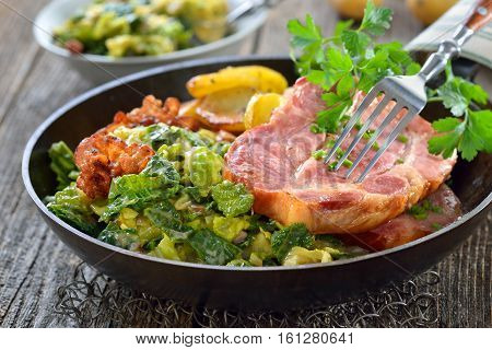 Smoked neck of pork with savoy cabbage, bacon and fried potatoes served in an iron pan on a wooden table