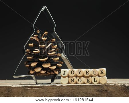 Baking tin Christmas tree shape with the French words Joyeux Noel Merry Christmas background on old wooden kitchen table
