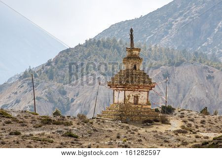 Traditional old Buddhist stupa on Annapurna Circuit Trek in Himalaya mountains, Nepal.