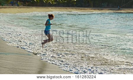 Young woman with long red hair play with waves running, feeling the sea, seascape beach of Dominican Republic, wide angle, Caribbean sea