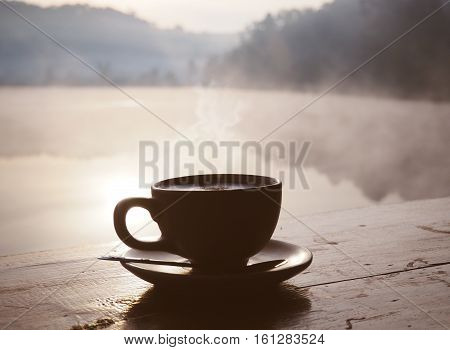 Silhouette cup of coffee at sunrise in the morning over mountain and lake background.