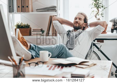 Enjoying little break. Handsome young man with closed eyes holding hands behind head and resting with feet on desk while sitting on working place in creative office