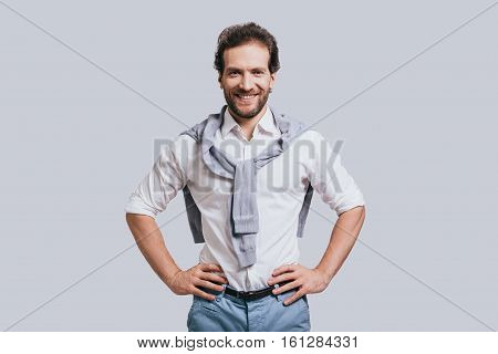 Young and successful. Beautiful young man in smart casual clothes keeping hands on hip and looking at camera while standing against grey background