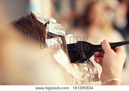 hairdresser coloring hair in studio