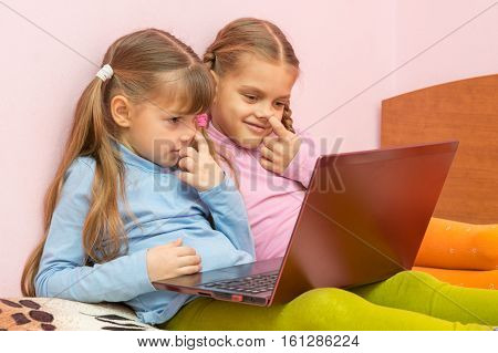 Two Girls Picking His Nose And Looking At A Laptop Screen