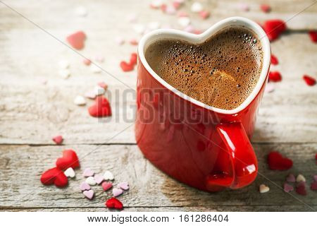 Tasty Coffee Espresso in a Heart Shape Red Cup on a Wooden Background. Love or Valentine's Day Concept.
