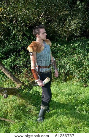 Medieval archer with chain shirt outdoors and holds drinking horn in hand