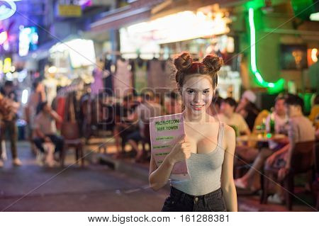 BANGKOK, THAILAND - FEBRUARY 23, 2016: Thai waitress at Khao San Road by night in Bangkok.  Khao San Road is a world famous backpacker street.