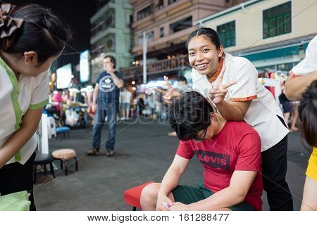 BANGKOK, THAILAND - FEBRUARY 24, 2016: Shoulder massage at Khao San Road by night in Bangkok.  Khao San Road is a world famous backpacker street.