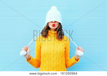 Happy Cool Girl Blowing Red Lips Makes Air Kiss Wearing A Knitted Hat, Yellow Sweater Over Blue Back