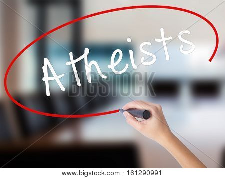 Woman Hand Writing Atheists With A Marker Over Transparent Board