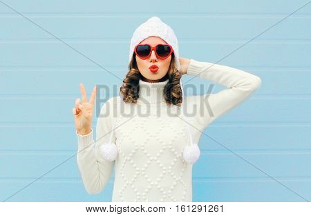 Woman Blowing Red Lips Makes Air Kiss Wearing A Heart Shape Sunglasses, Knitted Hat, Sweater Over Bl