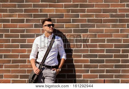 style and people concept - young man in sunglasses with bag over brickwall