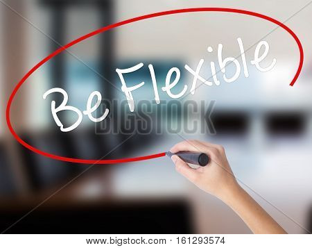 Woman Hand Writing Be Flexible With A Marker Over Transparent Board.